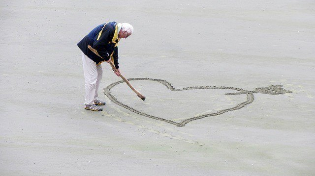 man drawing a heart on the beach